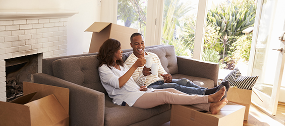 Couple sits on couch surround by moving boxes